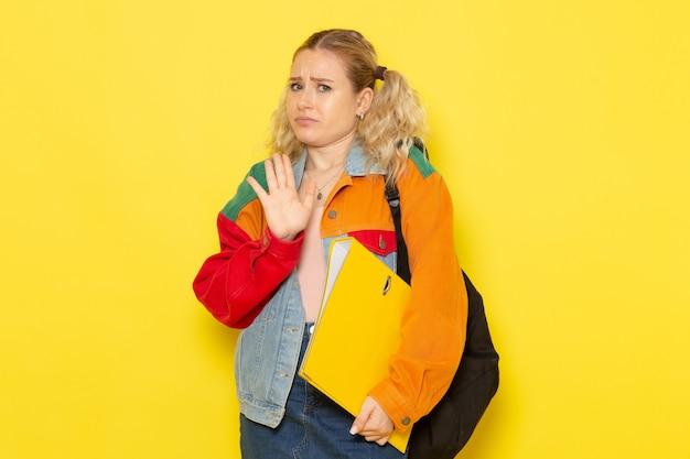 Vrouwelijke student jong in moderne kleding gewoon poseren met verwarde uitdrukking op geel