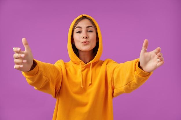 Vrouwelijke student, jonge dame met blij gezicht, capuchon aan, laat zien dat ze een knuffel en kus wil. oranje hoodie en ringen dragen