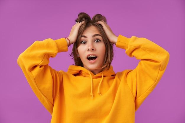 Vrouwelijke student, jonge dame met donkerbruin kort haar, handen boven haar hoofd. geschokt kijkend, paniekmeisje over paarse muur. oranje hoodie, tandenbeugels en ringen dragen