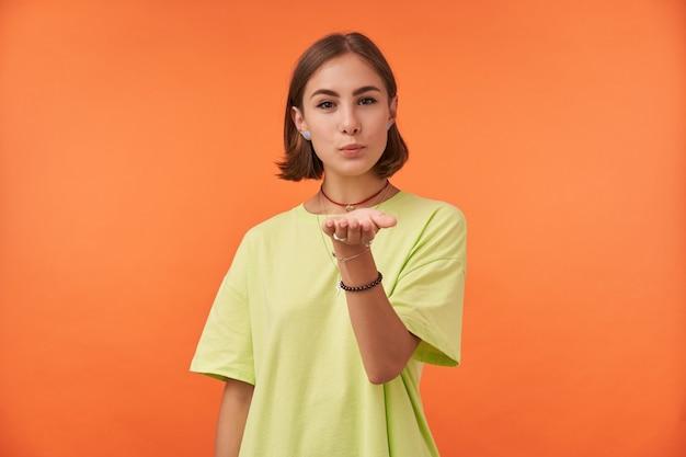 Vrouwelijke student, jonge dame met kort donkerbruin haar dat over oranje muur wordt geïsoleerd. kus verzenden, interesse tonen. groen t-shirt, ketting, armbanden en ringen dragen