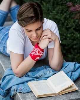 Vrouwelijke student leesboek liggend op parapet