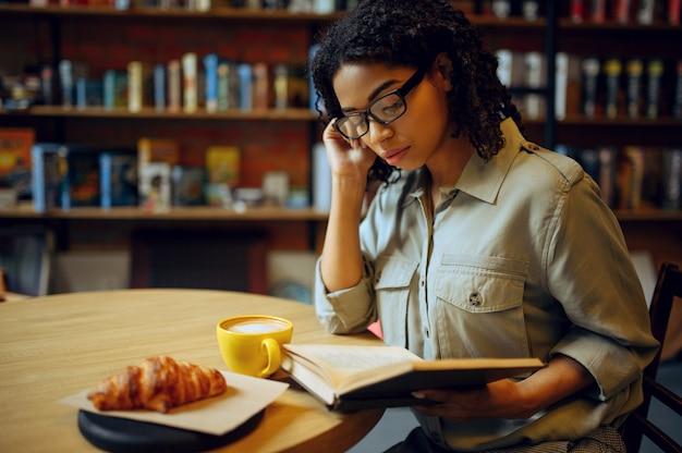Vrouwelijke student leest boek in bibliotheekcafé. vrouw aan tafel met koffie en croissants, onderwijs en kennis. meisje studeert op de campus