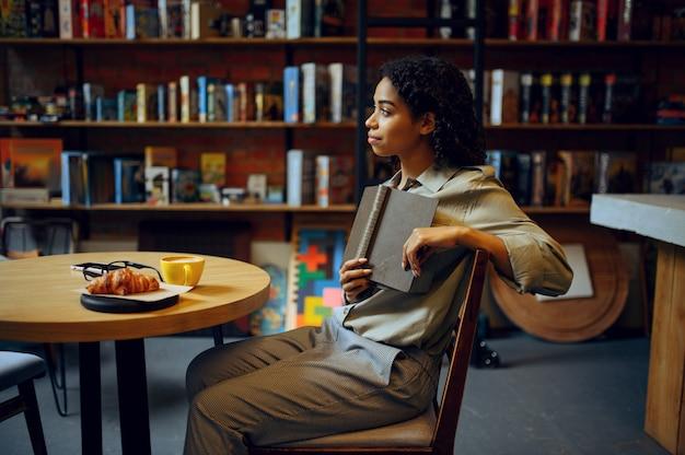Vrouwelijke student leest boek in bibliotheekcafé