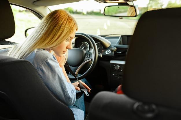 Vrouwelijke student maakt de veiligheidsgordel vast in de auto, rijschool. man die een vrouw leert voertuig te besturen. rijbewijs opleiding