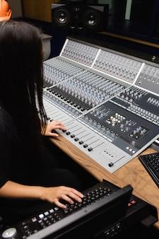 Vrouwelijke student met behulp van geluid mixer