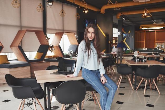 Vrouwelijke student met behulp van laptop zittend in café. geconcentreerde jonge vrouw freelancer op het werk.