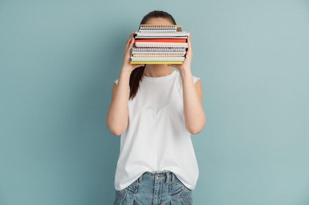 Vrouwelijke student met een berg notitieboekjes en boeken in haar handen