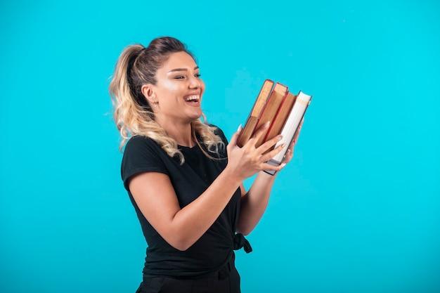 Vrouwelijke student met een grote voorraad boeken en voelt zich positief