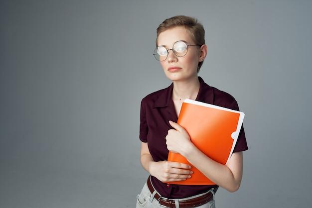 Vrouwelijke student met een oranje map in de hand bijgesneden weergave