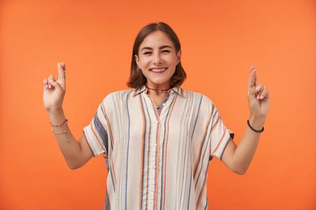 Vrouwelijke student met kort donkerbruin haar die vingers kruisen en glimlachen, gestreept overhemd, tandensteunen en armbanden dragen.