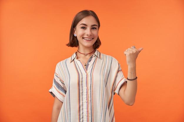 Vrouwelijke student met korte donkerbruine haarglimlach die naar rechts op exemplaarruimte richt