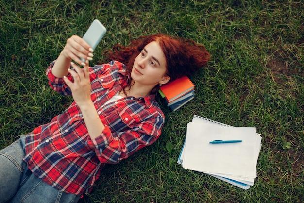 Vrouwelijke student met mobiele telefoon liggend op het gras in zomer park.