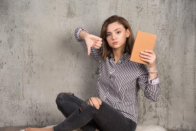 Vrouwelijke student met oranje boek duimen naar beneden geven.