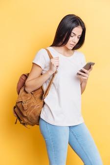 Vrouwelijke student met rugzak die smartphone over gele muur gebruikt