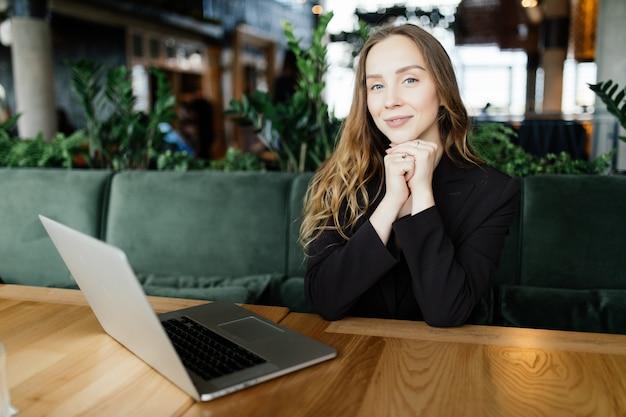 Vrouwelijke student met schattige glimlach toetsen iets op netbook terwijl u ontspant na colleges aan de universiteit, mooie gelukkige vrouw die op laptop werkt tijdens koffiepauze in café-bar