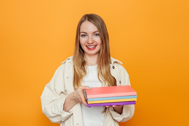 Vrouwelijke student met veel boeken geïsoleerd over oranje studio achtergrond