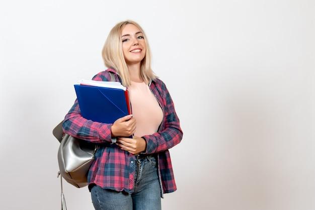 Vrouwelijke student met verschillende bestanden met een glimlach op wit