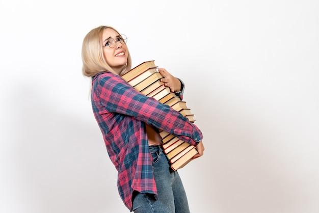 Vrouwelijke student met verschillende zware boeken op wit
