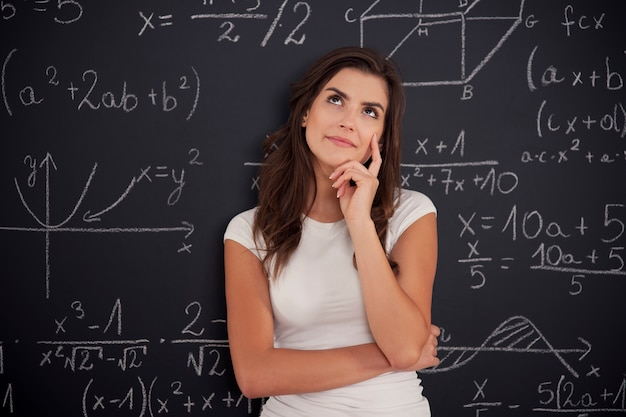 Vrouwelijke student na te denken over wiskundeprobleem
