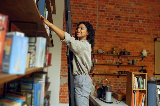 Vrouwelijke student neemt boek van plank in universiteitsbibliotheek. vrouw bij boekenplank, onderwijs en kennis. meisje studeert op de campus