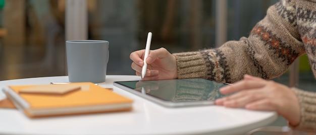 Vrouwelijke student online leren met mock-up tablet en briefpapier op salontafel