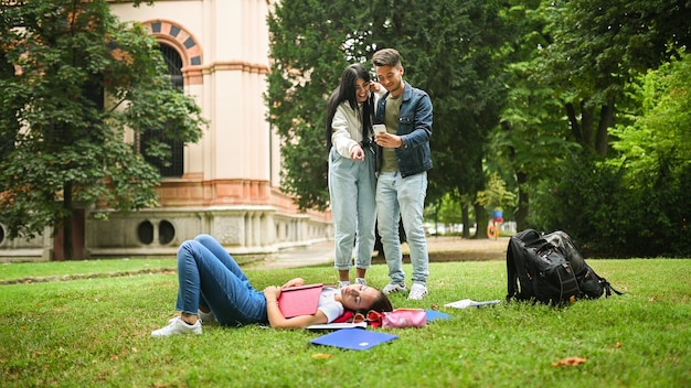 Vrouwelijke student slaapt op het gras terwijl haar vrienden foto's van haar maken