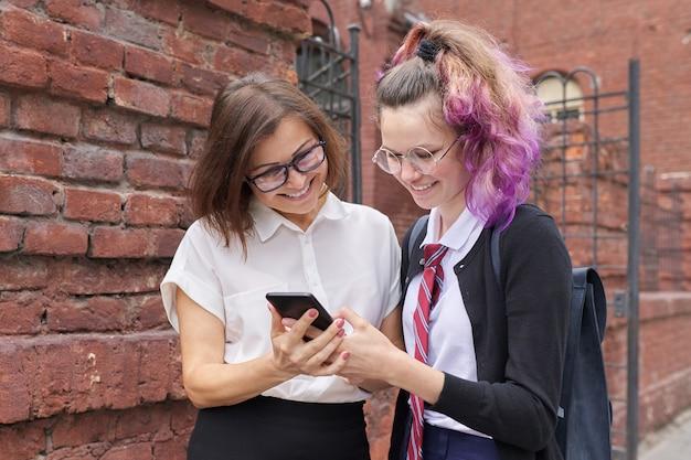 Vrouwelijke student tiener in schooluniform met rugzak wandelen praten met vrouw leraar