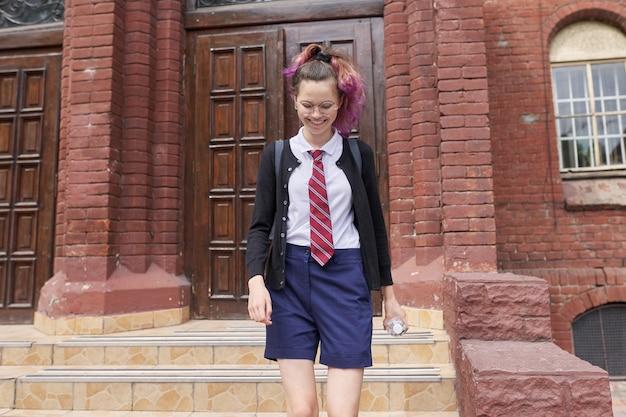 Vrouwelijke student tiener in uniform met rugzak, school achtergrond bouwen. terug naar school, terug naar school, onderwijs, tieners concept
