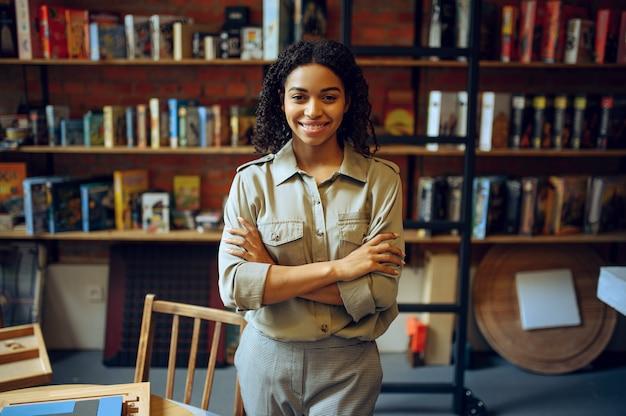 Vrouwelijke student vormt op de plank in de universiteitsbibliotheek. vrouw bij boekenplank, onderwijs en kennis. meisje studeert op de campus