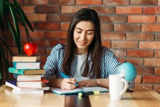 Vrouwelijke student zit aan de tafel met leerboeken