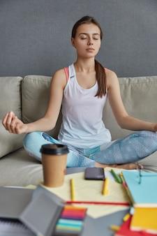 Vrouwelijke student zit in lotushouding, voelt rustademhaling, vindt inspiratie in meditatie, drinkt koffie