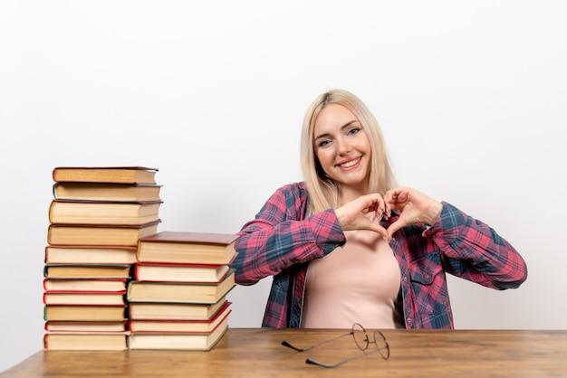 Vrouwelijke student zitten met verschillende boeken lachend op wit