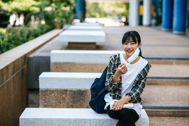 Vrouwelijke student zittend op de trap en een boek gelezen.