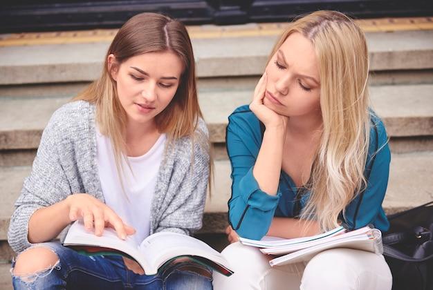 Vrouwelijke studenten buiten met boek