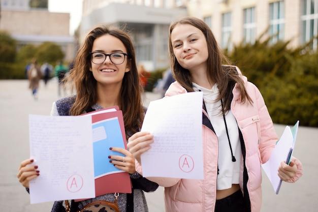 Vrouwelijke studenten die papers tonen met een perfect testresultaat, klasse a