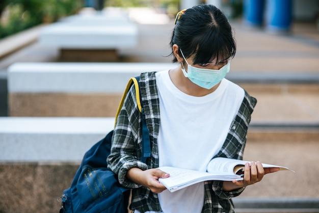 Vrouwelijke studenten dragen maskers en boeken op de trap.
