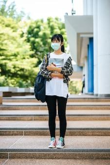 Vrouwelijke studenten dragen maskers, staan op trappen en houden boeken vast.