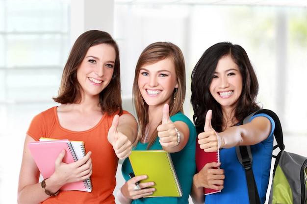 Vrouwelijke studenten samen duimen opdagen
