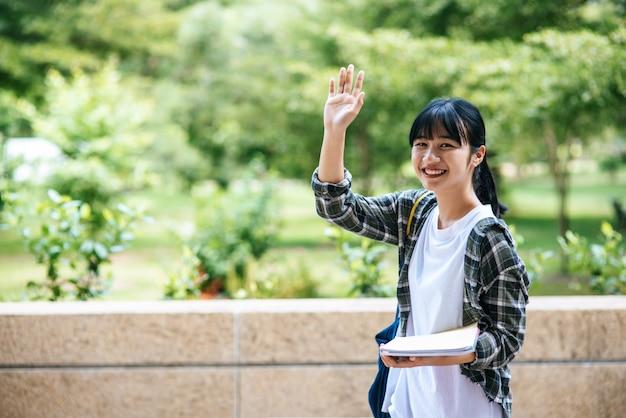 Vrouwelijke studenten staan op de trap en houden boeken vast.