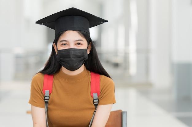 Vrouwelijke studenten, universitair afgestudeerden, dragen zwarte hoeden, gele kwastjes en dragen maskers tijdens de epidemie.