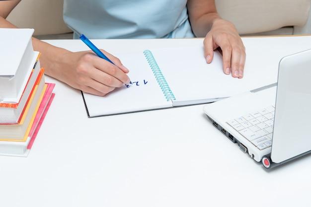 Vrouwelijke studentenhand die een pen vasthoudt, de opdracht in een notitieboekje schrijft, voor een laptop en boeken zit. examen voorbereiding concept. terug naar schoolconcept. thuis leerconcept