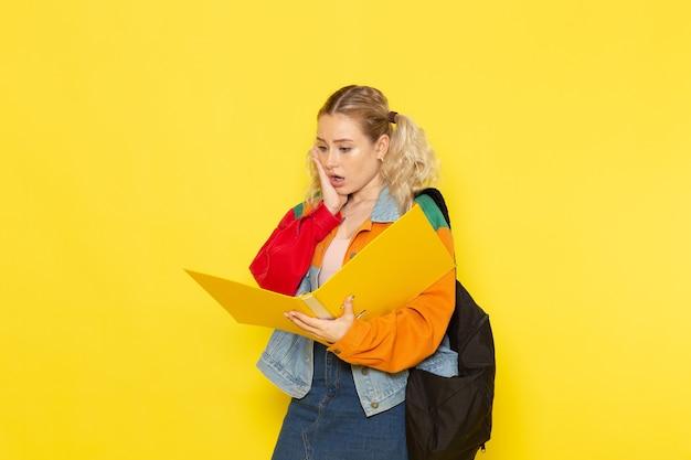 Vrouwelijke studentenjongeren in moderne kleren die dossier op geel controleren