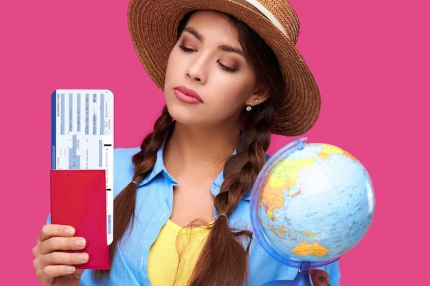 Vrouwelijke studentenreiziger die vliegtickets, paspoort en bol, geïsoleerde achtergrond houdt. studio opname. air vlucht reis concept