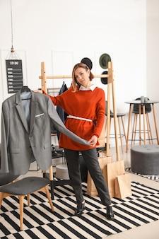 Vrouwelijke stylist met mannelijke kleding in haar atelier