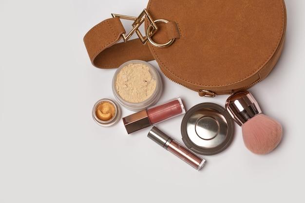 Vrouwelijke suède portemonnee met markeerstift, borstel, losse poeder en crème oogschaduw op een grijze achtergrond. ruimte voor tekst