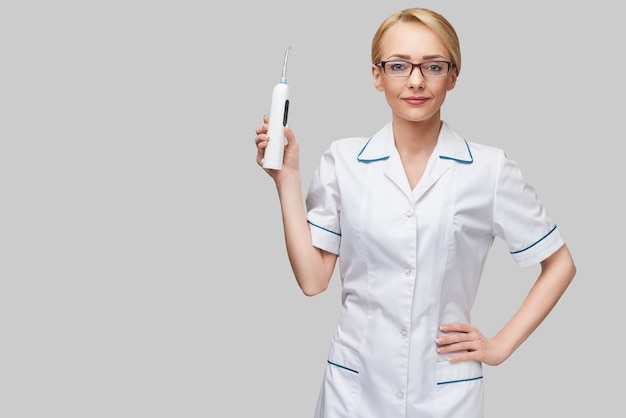 Vrouwelijke tandarts arts toont irrigator hygiëneapparatuur voor een zorgvuldige tandenreiniging