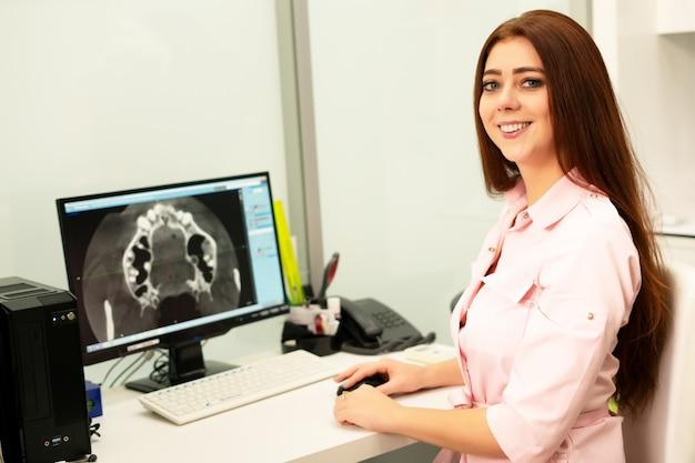 Vrouwelijke tandarts arts zit aan tafel op de computer een ct-scan van de kaak. de dokter is gekleed in professionele kleding.