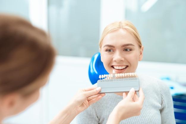 Vrouwelijke tandarts bepaalt de kleur van de tanden van de patiënt.