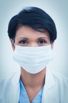 Vrouwelijke tandarts die chirurgisch masker draagt
