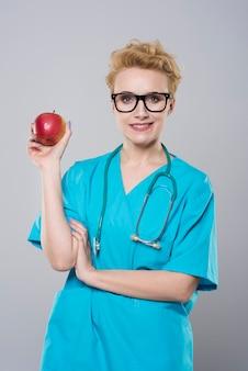 Vrouwelijke tandarts die een appel houdt